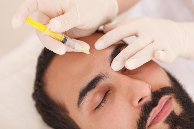 남성 고객의 이마 주름에 얼굴 필러를 주입하는 미용사의 클로즈업 프리미엄 사진