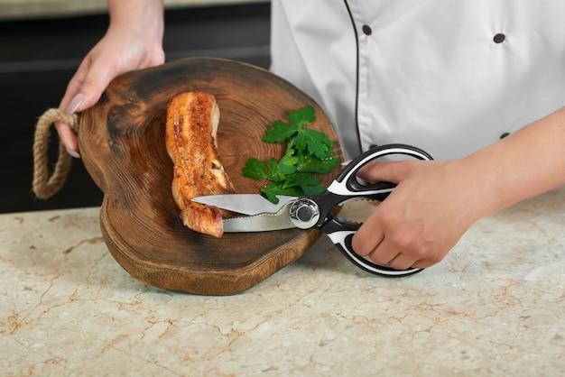 レストランのキッチンで働くハサミで焼き肉を切る女性シェフのクローズアップをトリミングしました。