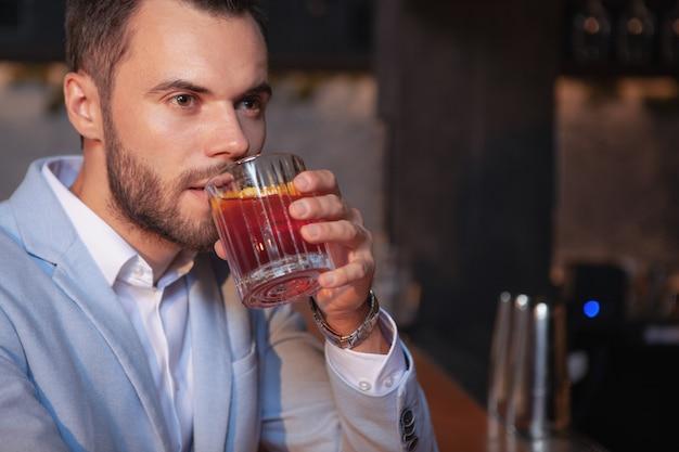 Обрезается крупным планом красивый бородатый элегантный мужчина пьет коктейль виски в баре