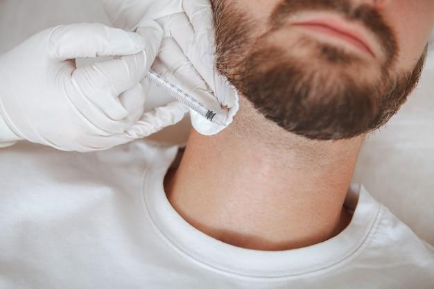 美容クリニックで美容師による首のしわフィラー注射を受けている男性のクライアントのトリミングされたクローズアップ