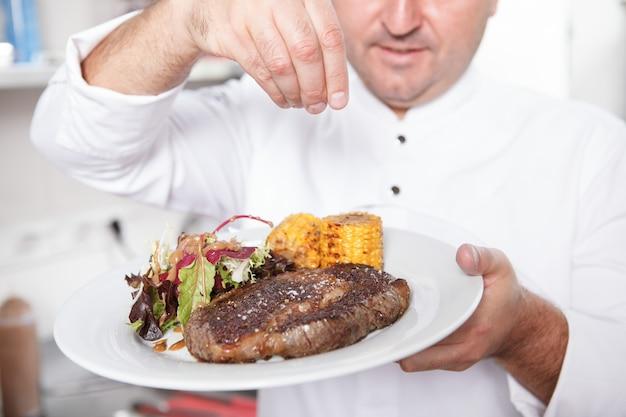 Обрезанный крупным планом вкусный жареный стейк из говядины на тарелке в руках шеф-повара