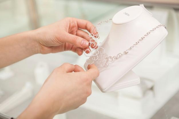 販売のためのダイヤモンドのネックレスを調べる女性の手のトリミングされたクローズアップ