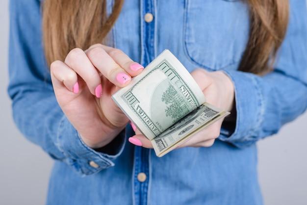 デニムの服を着て古いお金を計算することを保持している指に長い爪ピンクの明るいマニキュアで女の子らしい美しい手のトリミングされたクローズアップは灰色の壁を分離しました