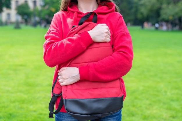 두 손으로 고등학교 근처 그녀의 가방을 포옹하는 사람의 자른 된 클로즈업. 푸른 잔디는 벽에