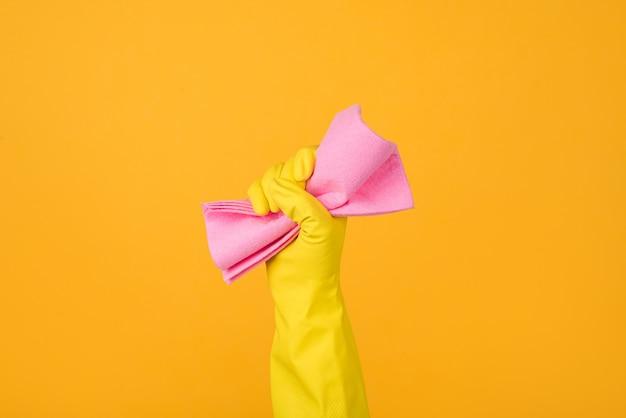 黄色の背景に分離されたダスティングのためのピンクのゴムを保持している黄色の手袋で手のトリミングされたクローズアップ写真。ハウスキーピングのコンセプト