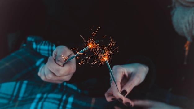 Обрезанное фото крупным планом бенгальских огненных палочек, сверкающих, горящих, руки влюбленных, держащих огненные палки вместе, встречи