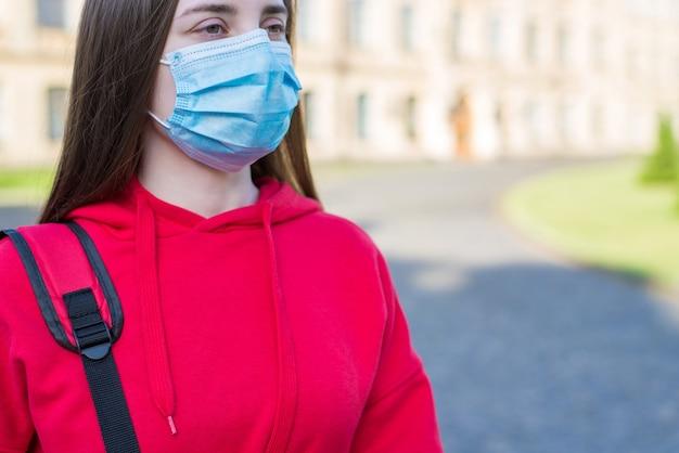 밖에서 수술용 마스크를 사용하여 평상복을 입고 생각에 잠긴 십대 소녀의 잘린 클로즈업 사진