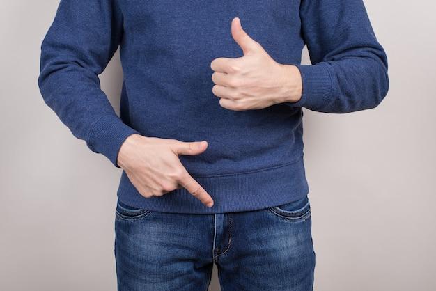 회색 배경에 격리된 바지 바지를 입고 자신의 오르간을 가리키는 만족한 자신감 넘치는 멋진 남자의 클로즈업 사진