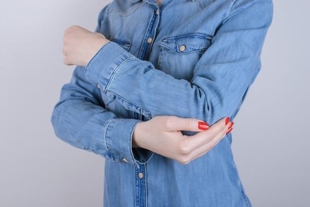 Обрезанное фото несчастной страдающей от боли дамы, касающейся локтя, изолированной на сером фоне, крупным планом, в повседневной джинсовой джинсовой одежде