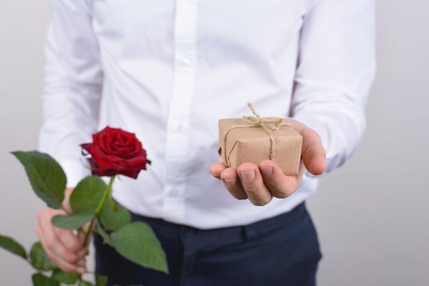 小さな小さなプレゼントと明るいバラの孤立した灰色の背景を保持しているハンサムな魅力的な幸せな陽気なポジティブな男の肖像画のクローズアップ写真をトリミング