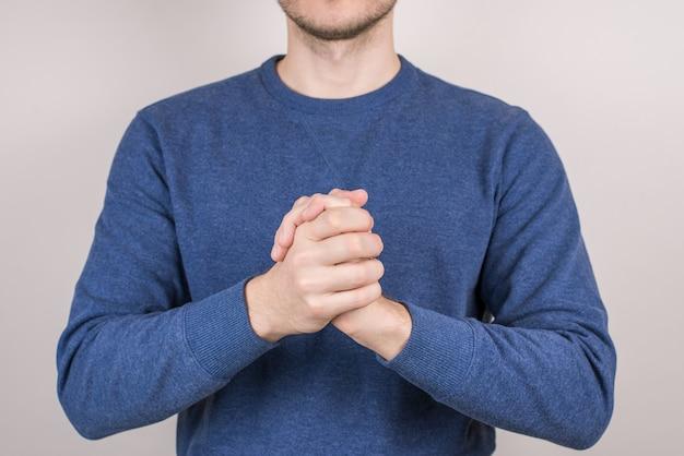 Обрезанный крупным планом фото портрет счастливого уверенного парня, объединяющего руки ладонями вместе, изолированный серый фон