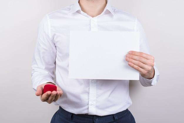 Обрезанный портрет крупным планом счастливого возбужденного веселого парня, держащего в руках белый рекламный щит, показывающий copyspace на изолированном сером фоне