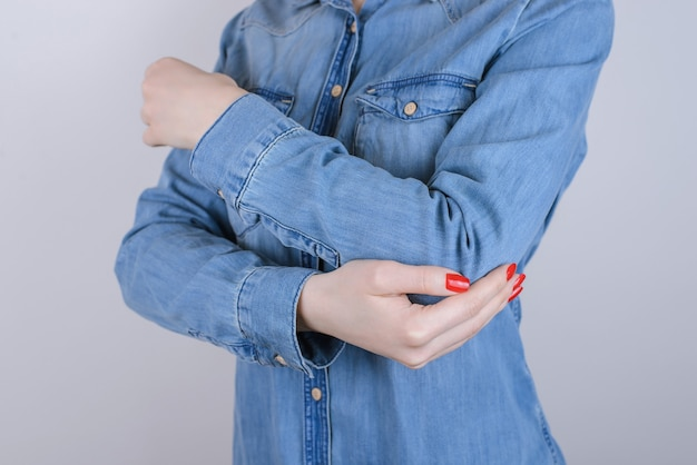 Cropped close up photo of unhappy suffering from pain lady touching elbow isolated on gray background copy-space wearing casual denim jeans clothing