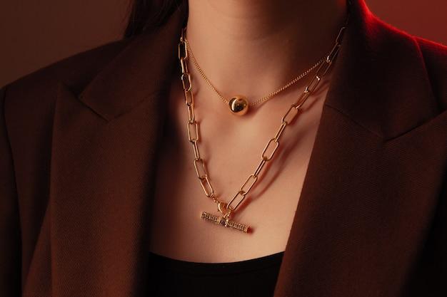 Обрезанный крупным планом портрет молодой женщины с идеальной шелковистой кожей, демонстрирующей золотую ювелирную цепочку с медальоном на шее в коричневой куртке.