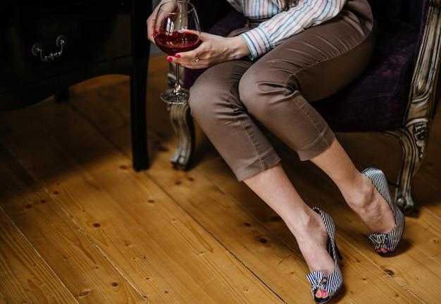 와인의 유리를 가진 초상화 여자를 가까이 자른