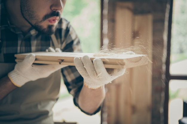Cropped close up  serious confident man blowing sawdust away from wooden block before polishing
