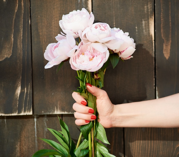 Cropped close up shot of a bouquet of pink peonies in a female hand wooden background