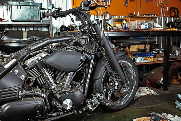Обрезать крупным планом выстрел из красивых и на заказ мотоцикла в мастерской
