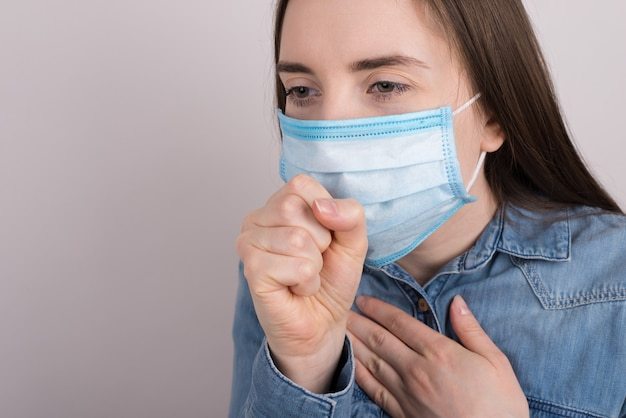 Cropped close up side profile view photo of sad upset unhappy woman in jeans shirt coughing holding hand fist near mouth face isolated grey background with copy empty space
