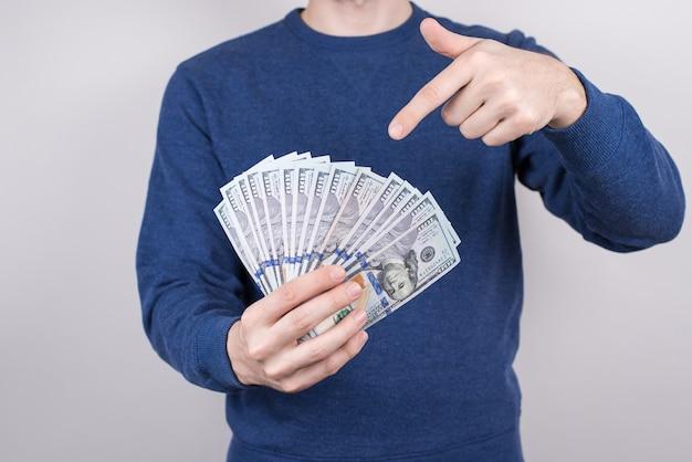 Обрезанное студийное фото крупным планом уверенного удачливого студента, демонстрирующего много денег, получающих зарплату за работу с частичной занятостью, изолированный серый фон