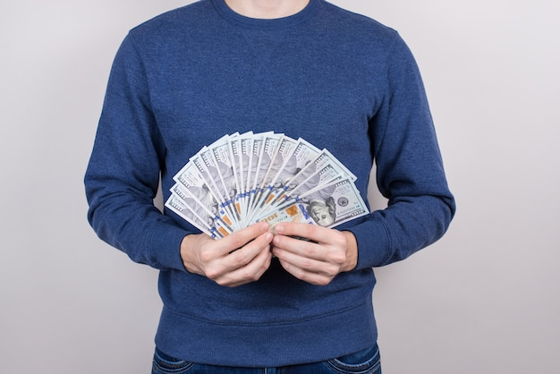 Обрезанное студийное фото крупным планом довольного парня, который знает, как зарабатывать деньги, изолированный серый фон