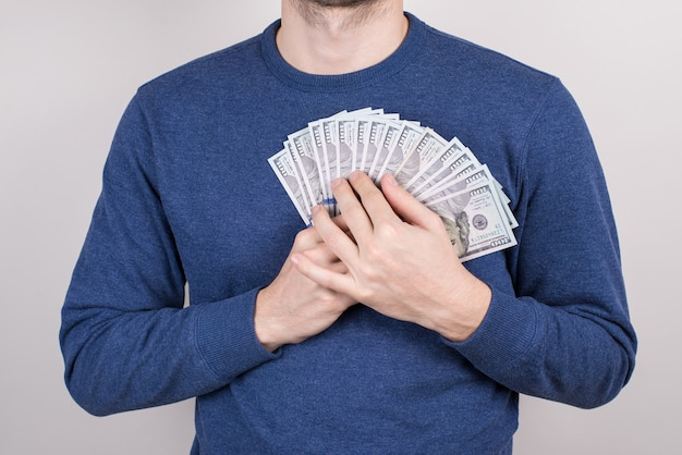 Cropped close-up studio photo shot of guy falling in love with money holding heart chest isolated grey background
