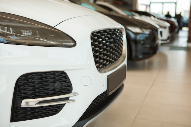Cropped close up of unrecognizable new cars parked at dealership