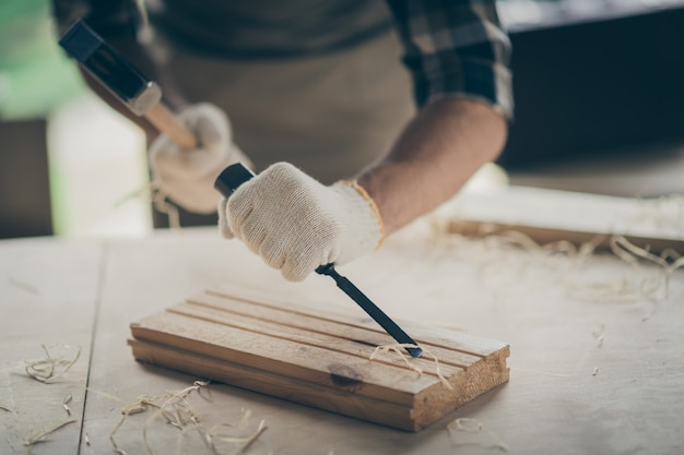 Cropped close-up view of his hands experienced professional guy specialist expert designer creating project start-up new modern home house things decor using hammer on table desk