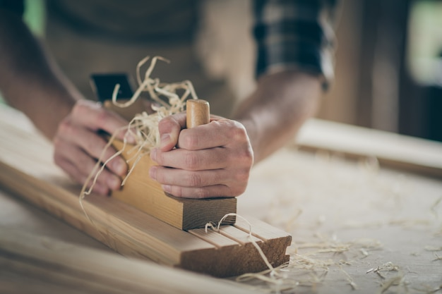 Cropped close-up view of his hands hardworking builder repairman specialist expert entrepreneur making home decor carving wood developing project on table desk