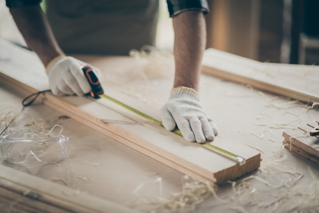 Cropped close-up view of his he nice hands swearing gloves skilled experienced guy expert measuring plank board building new house project start-up at modern industrial loft style interior indoors