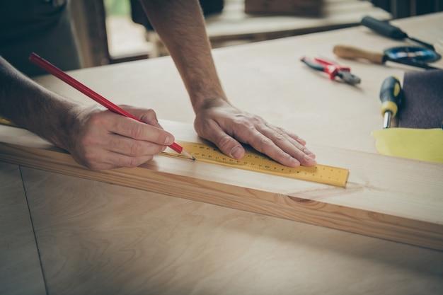 그의 좋은 전문 숙련 된 열심히 일하는 사람의 자른 확대보기 집에서 보드 판자 건물 프로젝트를 측정하는 마크를 만드는 현대 산업 로프트 벽돌 스타일 인테리어 실내