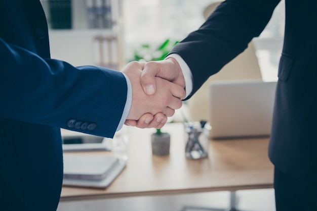Cropped close-up view of two male qualified expert employer hr shaking hands hiring vacancy human resources deal done teamwork at light white interior workplace workstation