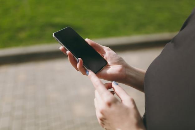 Ritagliato primo piano delle mani della donna che tengono e utilizzano il telefono cellulare, smartphone con schermo vuoto vuoto nel parco cittadino all'aperto