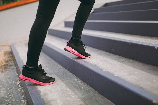 Cropped close up of woman legs in sportswear, black and pink sneakers doing sport exercises, climbing on stairs outdoors