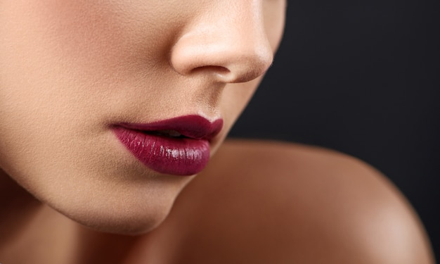 Cropped close up of woman's lips covered with dark lipstick.