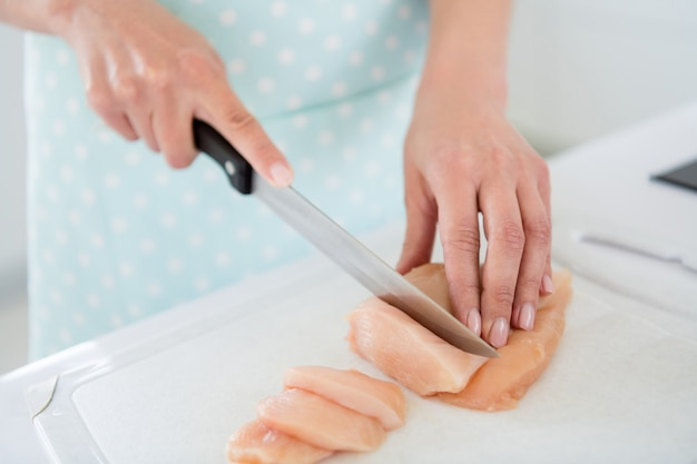 Cropped closeup photo of housewife hands cutting chicken meat weekend cooking tasty dinner preparation waiting family back home white light kitchen indoors