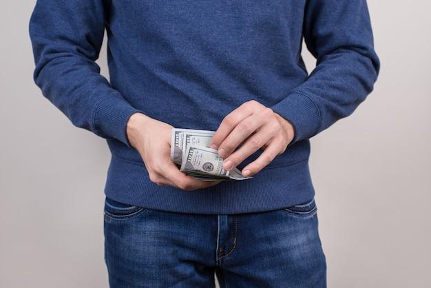 Обрезанное фото крупным планом уверенного в себе парня в синем свитере, пуловер, держащего стопку денег в руках в джинсовой одежде, изолированный серый фон