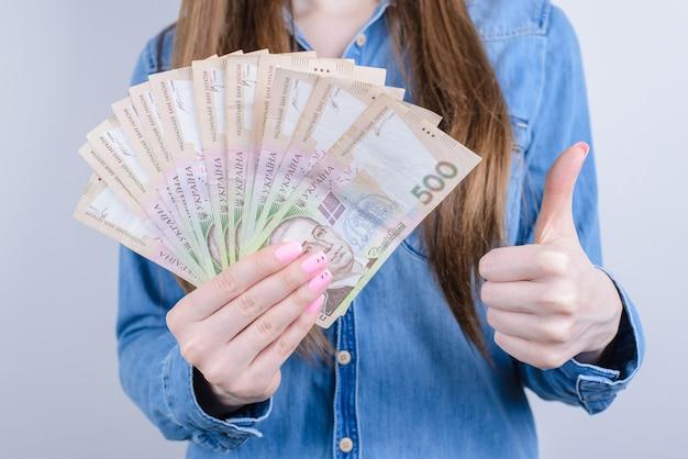 Обрезанное фото крупным планом довольных радостных позитивных веселых счастливых деловых людей, показывающих, что они дают сделать палец вверх, рекламные стопки денег, изолированные на сером фоне