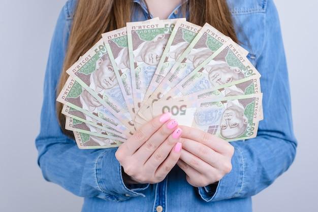Обрезанное фото крупным планом украины деньги, держа в руках красивая дама, изолированные на сером фоне Premium Фотографии
