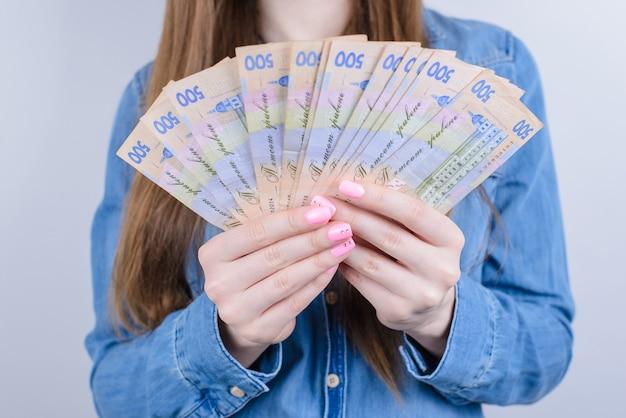 Обрезанное фото крупным планом украины деньги, держа в руках красивая дама, изолированные на сером фоне