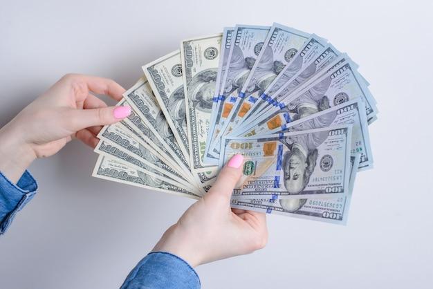 Обрезанные крупным планом фото портрет руки, держащей подсчет наличных денег сша, изолированные на сером фоне