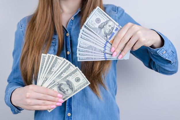 Обрезанное фото крупным планом счастливой удовлетворенной очаровательной красивой женщины, которая хвастается грудой стопки денег в руках в джинсовой повседневной рубашке, изолированной на сером фоне