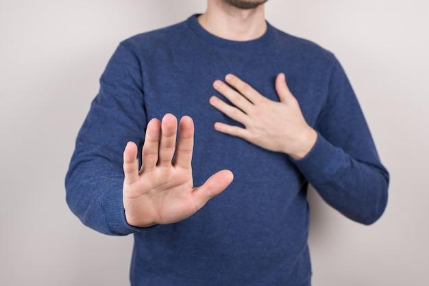胸の孤立した灰色の背景にカメラの前で手をつないでいる不幸な悲しい動揺の男のトリミングされたクローズアップスタジオ写真の肖像画