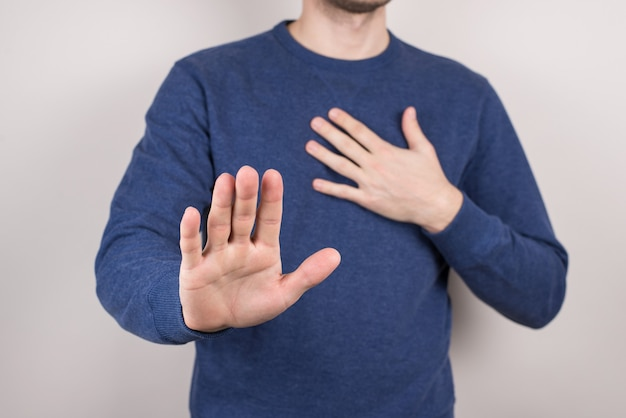 Cropped closeup studio photo portrait of unhappy sad upset guy making holding hand in front of camera on chest isolated grey background