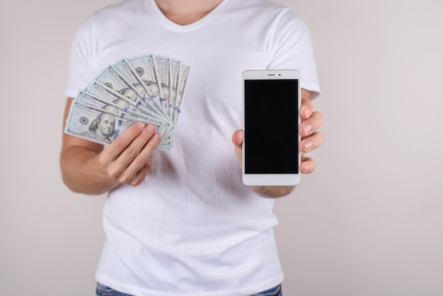 Cropped closeup view studio photo portrait of happy satisfied glad rich wealthy confident macho boyfriend giving you mobilephone blurred isolated grey wall