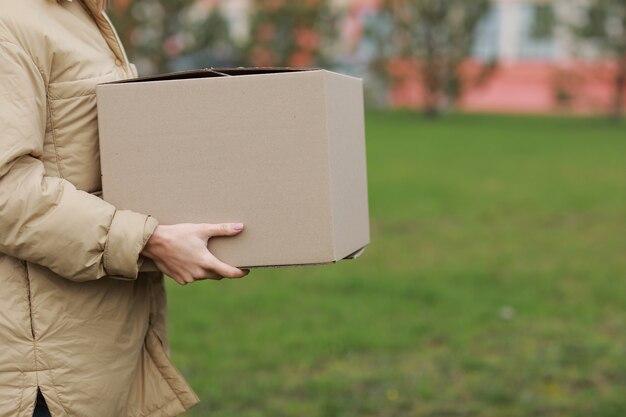 자른 배달 소녀 주거 복잡 한 배경에 야외에서 빈 골 판지 상자를 개최.