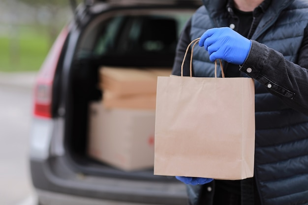 Cropped delivery man in gloves hold paper bag near the car outdoor