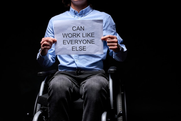 Cropped disabled man can work as anyone else, holding paper job search. isolated black background