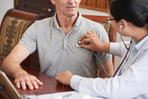 Cropped doctor checking up the heartbeat of senior patient