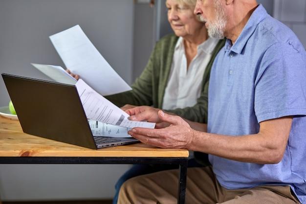 家族の1か月の予算を一緒に管理し、コンピューターバンキングアプリケーションを使用して夫婦に焦点を合わせ、台所で紙幣を数える、トリミングされた老人と女性。ノートパソコンと手に焦点を当てる